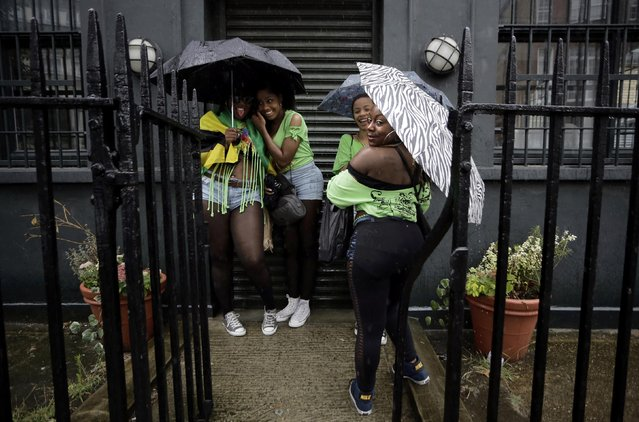 Revellers protect themselves from a rain storm  at the Notting Hill Carnival in London August 25, 2014. (Photo by Kevin Coombs/Reuters)