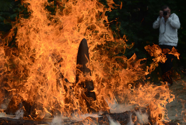A journalist takes a photo of more then 33 kg of rhinoceros horns as they burn at a Zoo in Dvur Kralove, Czech Republic, on September 19, 2017. A Czech zoo on Tuesday burnt 33 kilos (72 pounds) of rhino horns, including some it had sawed off its own animals in the wake of a brutal attack on a French zoo The rhino horn burning event hopes to send a strong anti- poaching message. (Photo by Michal Cizek/AFP Photo)