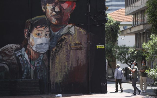 A newly painted mural shows a youth wearing a face mask, during a government ordered lockdown to prevent the spread of the new coronavirus in Bogota, Colombia, Monday, April 13, 2020. (Photo by Fernando Vergara/AP Photo)