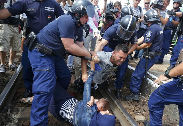 Hungarian policemen detain migrants on the tracks as they wanted to run away at the railway station in the town of Bicske, Hungary, September 3, 2015. (Photo by Laszlo Balogh/Reuters)