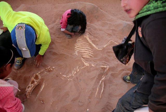 Children play with the replica of a dinosaur fossil at the Cretaceous park in Cal Orcko, on the outskirts of Sucre, Bolivia, July 22, 2016. (Photo by David Mercado/Reuters)