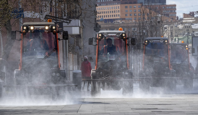 Municipal vehicles spray disinfectant on the deserted streets of central Moscow, on April 12, 2020 during a strict lockdown in Russia to stop the spread of the COVID-19, caused by the novel coronavirus. (Photo by Yuri Kadobnov/AFP Photo)