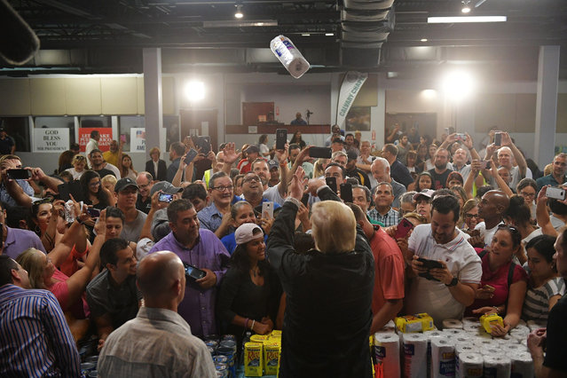 US President Donald Trump takes part in a food and suplly distribution at the Cavalry Chapel in Guaynabo, Puerto Rico on October 3, 2017. Nearly two weeks after Hurricane Maria thrashed through the US territory, much of the islands remains short of food and without access to power or drinking water. (Photo by Mandel Ngan/AFP Photo)