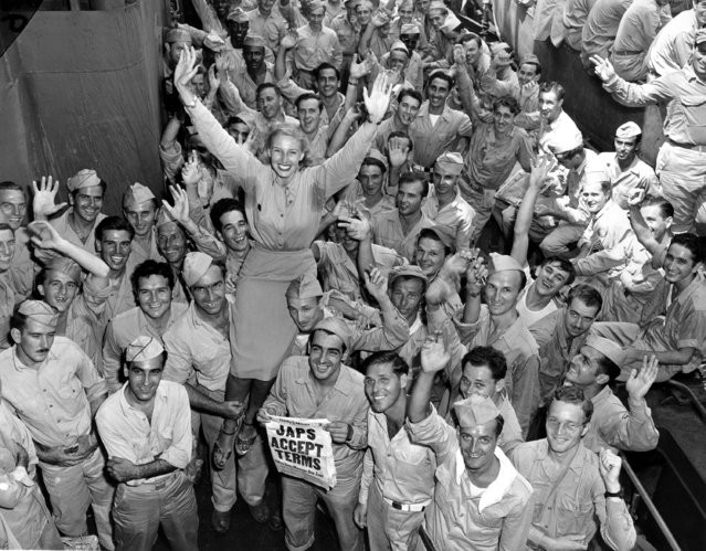 Candy Jones, a model who had been in the Pacific for ten months entertaining troops, arrives home with American soldiers from Pearl Harbor as they celebrate the Allied victory on the U.S. Navy transport in New York City on Aug. 14, 1945. The soldier at left, lifting Jones, is Gen. Charles H. Muir. (Photo by Murray Befeler/AP Photo)