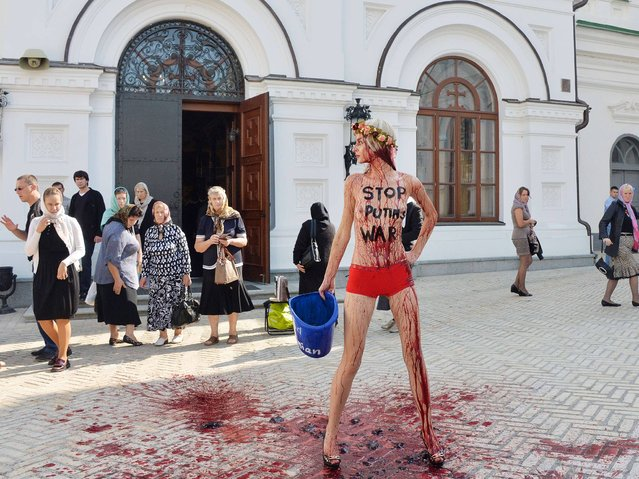 """A FEMEN activist with the inscription """"Stop Putin's war"""" on her body protests against the politics of Russia in Kiev Pechersk Lavra on September 11, 2014. (Photo by AFP Photo)"""