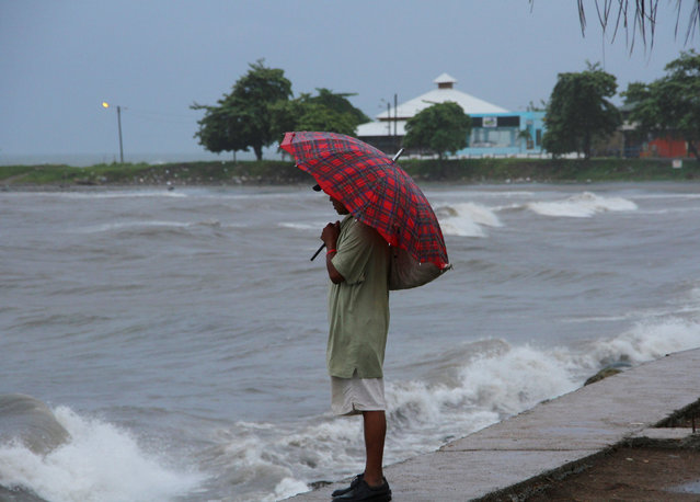 A man shields from the rain with an umbrella as Hurricane Earl passes the coast of La Ceiba, Honduras, August 3, 2016. (Photo by Reuters/Stringer)