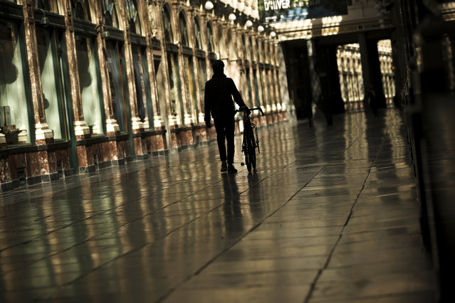 A man walks along along a virtually empty Royal Gallery of Saint Hubert commercial street during a partial lockdown ordered by Belgium government in Brussels, Tuesday, March 24, 2020. (Photo by Francisco Seco/AP Photo)