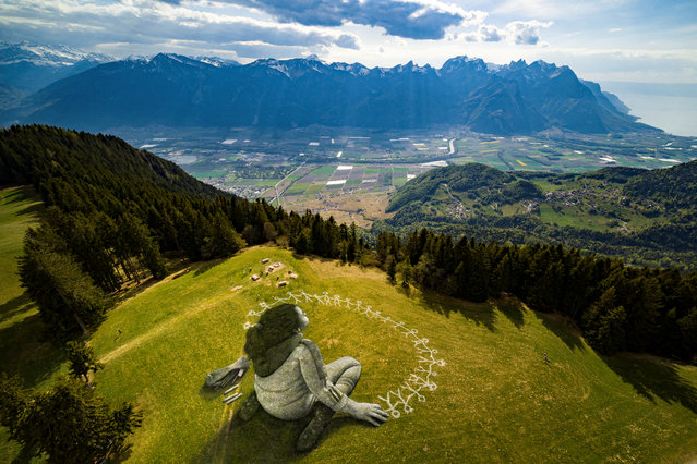 "An artwork called ""Beyond Crisis"" by French artist Guillaume Legros aka Saype and created with an eco paint made out of chalk and coal over a 3000 sqm field is pictured during the coronavirus disease (COVID-19) outbreak in Leysin, Switzerland, April 24, 2020 in this picture obtained by Reuters April 26, 2020. (Photo by Valentin Flauraud/SAYPE/Handout via Reuters)"