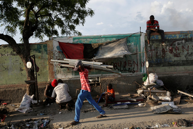 A man carrying pipes walks past a scrap metal stand along a street in Port-au-Prince, Haiti, July 14, 2016. (Photo by Andres Martinez Casares/Reuters)