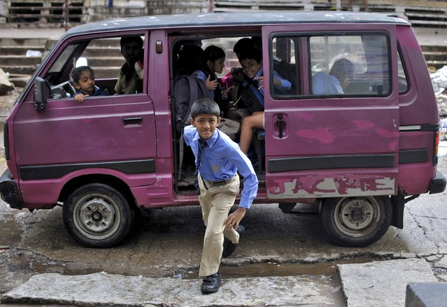 A schoolboy looks on as he alights from a private school van to collect his lunch box on the occasion of International Literacy Day in Bengaluru, India, September 8, 2015. (Photo by Abhishek N. Chinnappa/Reuters)