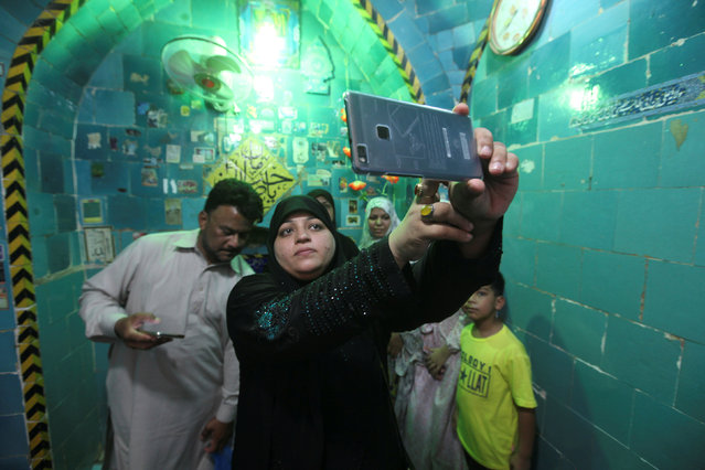 """A woman takes a selfie inside the shrine of Imam Mahdi at the Wadi al-Salam cemetery, Arabic for """"Peace Valley"""", in Najaf, south of Baghdad, Iraq, August 1, 2016. (Photo by Alaa Al-Marjani/Reuters)"""