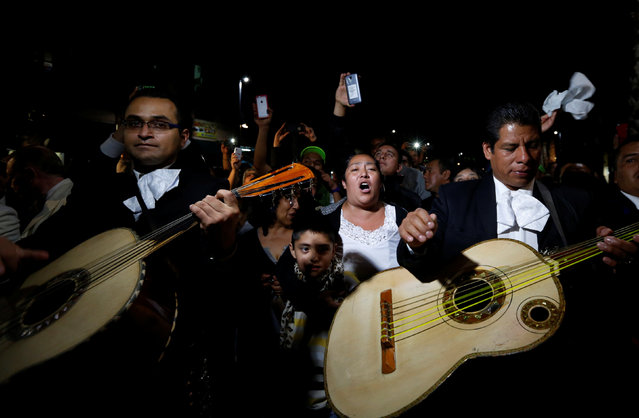 A mariachi band together with fans perform songs from iconic Mexican singer and song writer Juan Gabriel after his death, next to his statue in Plaza Garibaldi in Mexico City, Mexico August 28, 2016. (Photo by Carlos Jasso/Reuters)