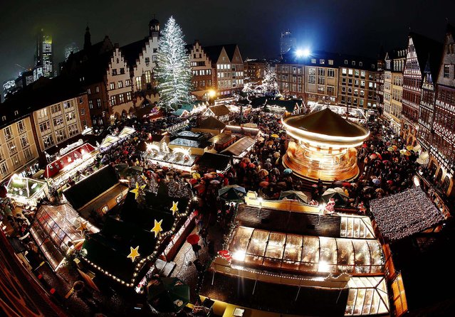 Hundreds of people gather in the rain to attend the opening of the traditional Christmas Market on Roemerberg Square in Frankfurt, Germany. (Photo by Michael Probst/Associated Press)