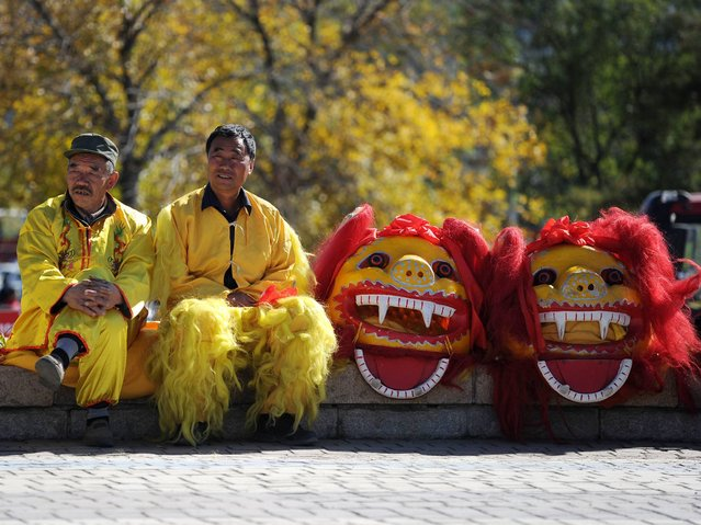 Two Chinese men wait to perform a lion dance at the start of the fourth stage of the 2014 Tour of Beijing cycling race in the suburbs of Beijing on October 13, 2014. The 2014 Tour of Beijing kicked off from the Zhangjiakou, in China's Hebei Province on October 10 with five stages throughout the capital city ending in the Bird's Nest Piazza on October 14. (Photo by Wang Zhao/AFP Photo)