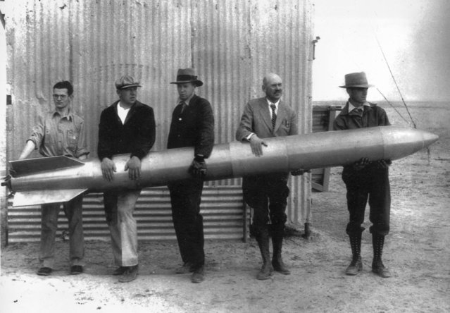 Holding one of the rockets designed to speed into the stratosphere at 700 miles an hour in search of new meteorological data, Dr. Robert Goddard, second from right, with a few of his assistants (unidentified), is pictured in Roswell, N.M., September 25, 1935. (Photo by AP Photo)