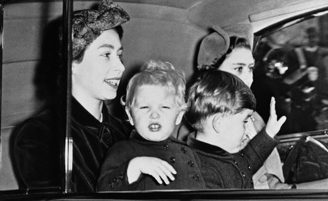 Britains Prince Charles waves a greeting to crowds outside London Railway Station as members of the Royal Family return from a holiday stay at Balmoral, Scotland on October 14, 1952. Little Princess Anne, on the lap of her smiling mother, Queen Elizabeth II appears ready to emulate her brother's wave although momentarily nonplused by photographers-flashes.  Princess Margaret, the Queen's sister, completes the royal group. (Photo by AP Photo)
