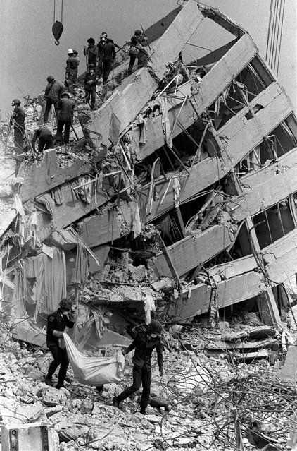 Soldiers carry a body bag from the rubble of Mexico City's Nuevo Leon apartments on Saturday, September 28, 1985, more than a week after a major earthquake which caused widespread destruction and left at least 9,000 dead. (Photo by Jeff Robbins/AP Photo)