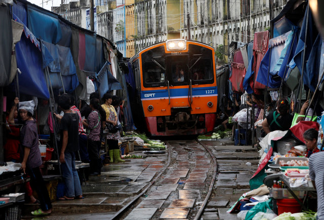 Thai vegetable market vendors pull back awnings and their produce off a railway track to allow a cross-country train to dissect through the middle of the town of Maeklong, in Samut Songkhram province, 60 km (37 miles) west of Bangkok August 16, 2012. (Photo by Chaiwat Subprasom/Reuters)