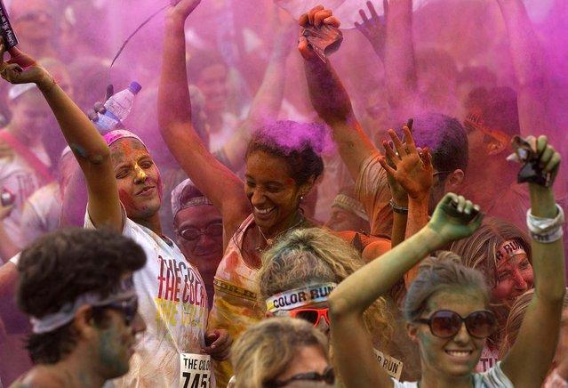 People dance after The Color Run 5K in Rio de Janeiro, December 16, 2012. (Photo by Silvia Izquierdo/Associated Press)