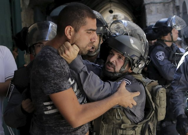 An Israeli policeman prevents a Palestinian man from entering the compound which houses al-Aqsa mosque, known by Muslims as the Noble Sanctuary and by Jews as the Temple Mount, in Jerusalem's Old City September 28, 2015. (Photo by Ammar Awad/Reuters)