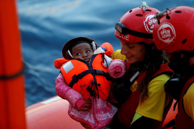A crew member of MV Open Arms, the search and rescue ship of Proactiva Open Arms, carries a migrant baby before passing it to crew members of MV Aquarius, a search and rescue ship run in partnership between SOS Mediterranee and Medecins Sans Frontieres, during a mid-sea transfer of migrants in the central Mediterranean off the coast of Libya, December 16, 2017. (Photo by Darrin Zammit Lupi/Reuters)