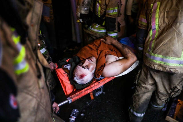 First responders carry away an injured person on a stretcher at the scene of an explosion at the Sina At'har health centre in the north of Iran's capital Tehran northern Tehran on June 30, 2020. (Photo by Amir Kholousi/ISNA/AFP Photo)