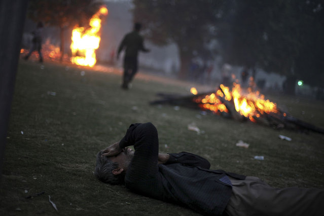 An Indian man overwhelmed by tear gas lies on the ground during a violent protest in New Delhi, on December 23, 2012. (Photo by Altaf Qadri/AP Photo)