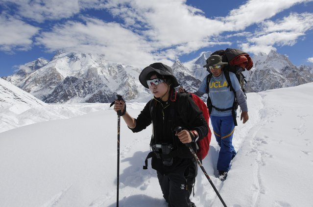 A porter guides his trekking client, 26-year old Yvonne Yip (L), from Hong Kong down the Baltoro glacier in the Karakoram mountain range in Pakistan September 7, 2014. (Photo by Wolfgang Rattay/Reuters)
