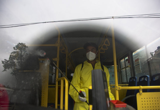A Nepalese bus driver disinfects his vehicle before starting service in Kathmandu, Nepal, Tuesday, July 14, 2020. After restrictions on public transportation for almost four month to control the spread of the new coronavirus, Nepal's government has allowed public vehicles to operate within certain districts and inside Kathmandu valley, following safety norms. (Photo by Niranjan Shrestha/AP Photo)
