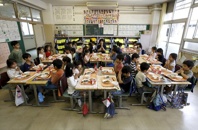 First grade students and their teacher Teruko Takakusaki pose for a photo during lunch at Takinogawa Elementary School in Tokyo, Japan, September 18, 2015. (Photo by Toru Hanai/Reuters)