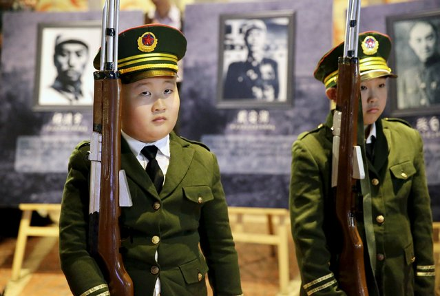 Children wearing uniforms hold toy guns during a military parade game on China's National Day, at Beyou World, a centre children where can experience different kinds of professions, in Beijing, October 1, 2015. (Photo by Reuters/Stringer)