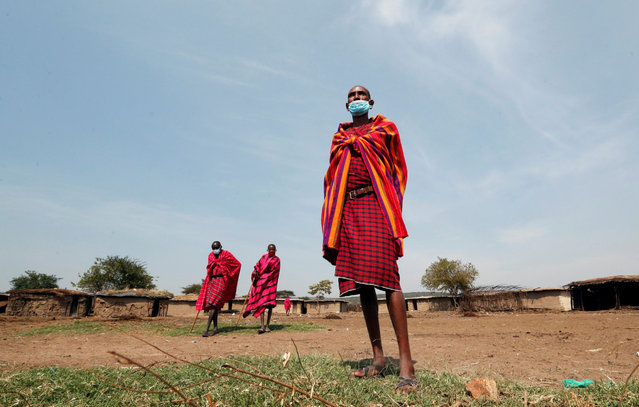 Maasai elders, wearing traditional costumes, with face masks on, due to the coronavirus disease (COVID-19) outbreak, gather at their homestead within the Orboma Manyatta in Sekenani, near the Maasai Mara game reserve in Narok County, Kenya on August 10, 2020. (Photo by Thomas Mukoya/Reuters)