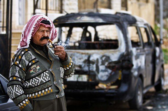A man smokes next to a torched car near the West Bank city of Ramallah on February 5, 2013. Two cars were set on fire and racist graffiti was sprayed in the village. (Photo by Majdi Mohammed/Associated Press)