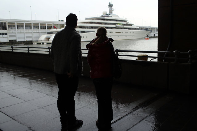 A couple looks out at the Eclipse, reported to be the largest private yacht in the world, which is docked at a pier in New York on February 19, 2013 in New York City. The boat, which measures 557ft in length and is estimated to cost 1.5 billion US dollars, is owned by Russian billionaire Roman Abramovich and arrived into New York on Wednesday.  (Photo by Spencer Platt)
