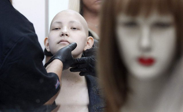 Hair stylist Marcelo Avatte prepares to fit Isidora Serrano, a 14-year-old who lost her hair due to chemotherapy to treat her bone cancer, with a natural hair wig in the cancer ward of the Luis Calvo Mackenna Hospital in Santiago, October 23, 2014. (Photo by Rodrigo Garrido/Reuters)