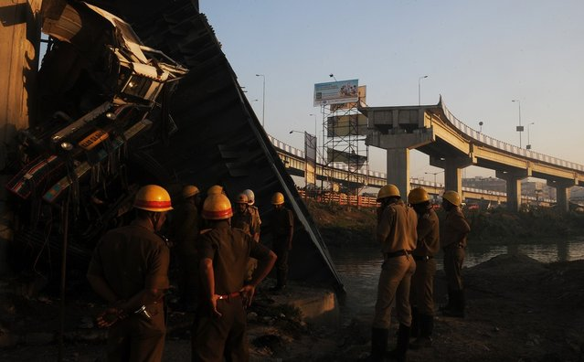 Indian onlookers and firefighters stand near the collapsed portion of a flyover in Kolkata on March 3, 2013. A huge portion of a flyover on the eastern side of the Indian metropolis collapsed leaving three persons injured, the flyover connects the airport with Eastern Metropolitan Bypass and the eastern and southern suburbs.   As the debris fell into a canal running below the flyover, it took down a truck the driver and two others were rescued from the canal by fire-brigade personnel and locals. (Photo by Dibyangshu Sarkar/AFP Photo)