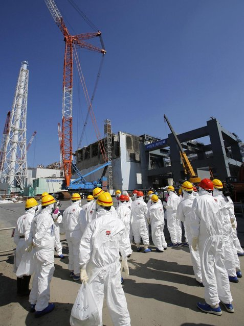 Members of the media wearing protective suits and masks are escorted by TEPCO employees while walking near the building housing the plant's No. 4 reactor, center, and an under construction foundation, right, which will store the reactor's melted fuel rods at Tokyo Electric Power Co.'s Fukushima Dai-ichi nuclear power plant in Fukushima prefecture, Wednesday, March 6, 2013, ahead of the second anniversary of the March 11, 2011 tsunami and earthquake. (Photo by Issei Kato/AP Photo/Pool)