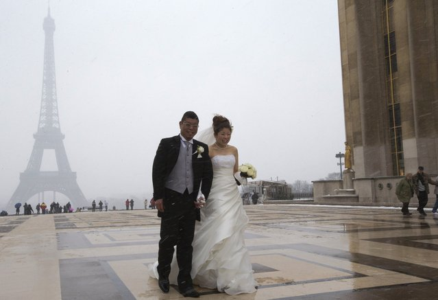 A young newly-wed Chinese couple  at the Trocadero plaza near the  Effeil in Paris, France, as they pose for  photographs in the snow Tuesday March 12, 2012. Hundreds of flights out of Western Europe have been cancelled, no trains are running under the English Channel, and Belgium's prince is stuck at home all because of a sudden dump of oddly late snowfall on Western Europe.  Less-prepared for the kind of heavy snow that regularly hits northern and eastern neighbors, cities across France, Belgium, southern England and Germany struggled Tuesday to assure transport amid the frosty conditions. (Photo by Jacques Brinon/AP Photo)