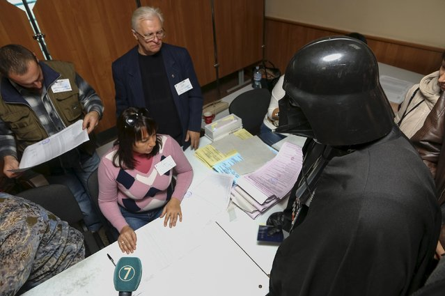 A person dressed as Star Wars character Darth Vader visits a polling station during a regional election in Odessa, Ukraine, October 25, 2015. Ukrainians go to the polls on Sunday to appoint mayors and council heads to regional seats. (Photo by Reuters/Stringer)