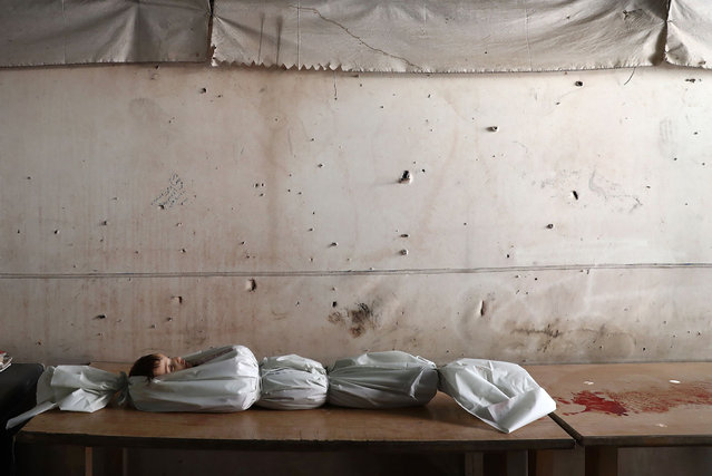 The body of a Syrian child lies on a table at a morgue on October 5, 2016, following reported air strikes on the rebel-held town of Douma, on the eastern outskirts of the capital Damascus. (Photo by Abd Doumany/AFP Photo)