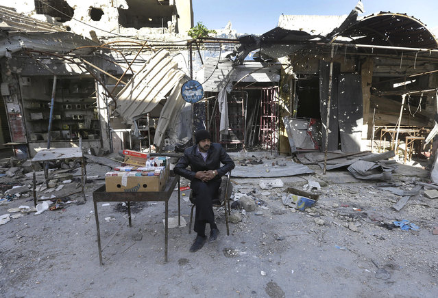 A Syrian street vendor who sells cigarette boxes, sits in front of destroyed shops which were damaged by the shelling of the Syrian forces, at Maarat al-Nuaman town, in Idlib province, on February 26, 2013. Syrian rebels battled government troops near a landmark 12th century mosque in the northern city of Aleppo on Tuesday, while fierce clashes raged around a police academy west of the city, activists said. (Photo by Hussein Malla/AP Photo /The Atlantic)