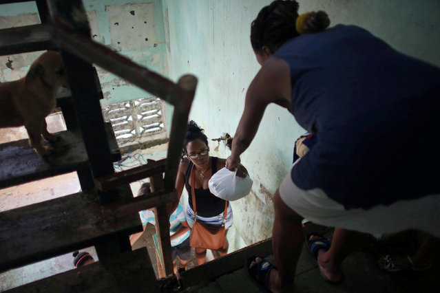 Yanet Maceo (L) helps her mother after the passage of Hurricane Matthew in Baracoa, Cuba October 7, 2016. (Photo by Alexandre Meneghini/Reuters)