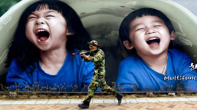 A South Korean soldier runs by a billboard during an anti-terror drills at Government Complex in Sejong South Korea, on April 17, 2013. (Photo by Lee Jin-man/Associated Press)