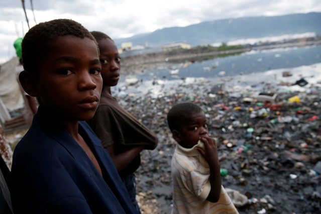 Children stand next to a flooded area after Hurricane Matthew passes Cite-Soleil in Port-au-Prince, Haiti, October 5, 2016. (Photo by Carlos Garcia Rawlins/Reuters)