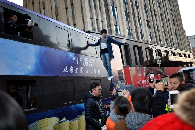 Magician Yif performs in front of Wanda Movie Park in Wuhan, Hubei province, December 16, 2014. (Photo by Reuters/China Daily)