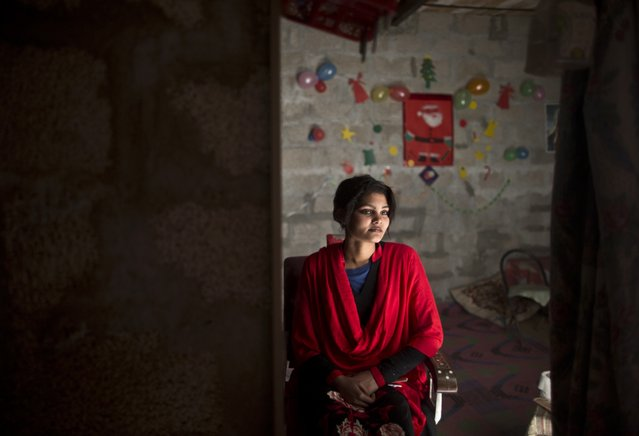Pakistani Christian Maria Akbar, 15, checks herself in the mirror, after having her make up done by hairdresser Razia Rehmat, 39, in preparation for Christmas holiday, at a hair salon, in a slum that hosts Christian families, on the outskirts of Islamabad, Pakistan, Wednesday, December 24, 2014. (Photo by Muhammed Muheisen/AP Photo)