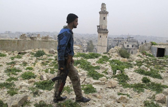 A rebel fighter carries his weapon as he walks in the old city of Aleppo near the frontline against forces loyal to Syria's President Bashar al-Assad December 28, 2014. (Photo by Jalal Al-Mamo/Reuters)
