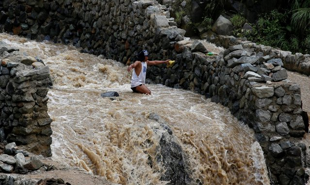 A local miner wades through water as he walks down from a mountain in Benguet a day after Typhoon Haima struck northern Philippines, October 21, 2016. (Photo by Erik De Castro/Reuters)