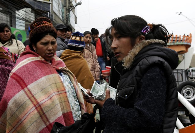A woman sells replicas of U.S. hundred dollar bills at a market in El Alto, on the outskirts of La Paz December 31, 2014. A stack of ten such bills is sold for one Bolivian peso and people buy them for good luck and fortune for the new year. (Photo by David Mercado/Reuters)