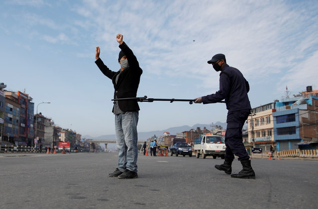A Nepalese police officer maintains distance as he detains a man defying the lockdown imposed by the government amid concerns about the spread of coronavirus disease (COVID-19), in Kathmandu, Nepal on March 29, 2020. (Photo by Navesh Chitrakar/Reuters)